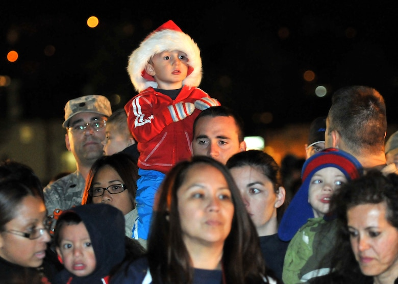 Onlookers observe as Col. Anita Latin, 61st Air Base Wing commander, reads a holiday story during the annual Tree Lighting Ceremony held at Fort McArthur, Dec. 4. Other festivities included a visit from Santa, snow day with children's play area covered with more than 20 tons of man-made snow and two 50-ft. sled runs. (Photo by Atiba S. Copeland)