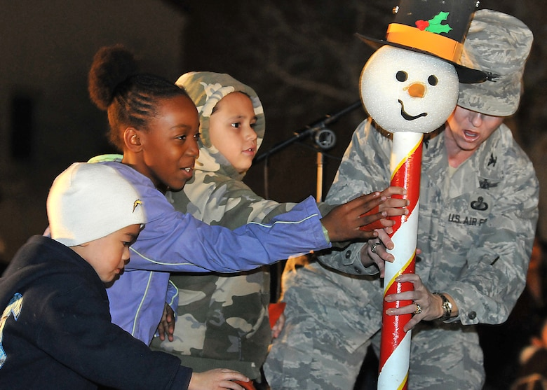 Col. Anita Latin, 61st Air Base Wing commander, with help from some children, switch on the lights to Fort McArthur's Christmas tree during the annual Tree Lighting Ceremony, Dec. 4. Other festivities included a visit from Santa, snow day with children's play area covered with more than 20 tons of man-made snow, two 50-ft. sled runs and a holiday story reading by Colonel Latin. (Photo by Atiba S. Copeland)