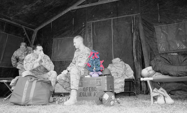 EGLIN AIR FORCE BASE, Fla. - Airmen from Team Eglin gather together to show a typical scene in deployed enviroments during the holiday season. Chief Master Sgt. Thomas Westermeyer, Command Chief, reminds people to remember our Team Eglin Warriors who are deployed during the holidays. As we enjoy this holiday season, let's remember that our family extends beyond those in our homes. Airmen united to build a tent in front of the Officers' Club and fill it with cots and other deployment items to give people perspective on the lives of the Warriors downrange. (U.S. Air Force photo illustration/Staff Sgt. Stacia Zachary)