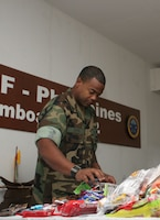Navy Aerographer's Mate 1st Class (AW/SW) Christopher Cross  from Joint Special Operations Task Force-Philippines sorts through bags of candy to put in nearly 600 stockings for JSOTF-P members. The items came from U.S. citizens, churches, non-profit organizations, and family members. (U.S. Marine Corps photo by Sgt. Jose Castellon/Released)