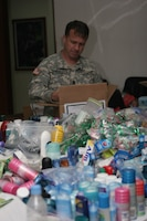 Command Sgt. Maj. Dave Randall, assigned to Joint Special Operations Task Force-Philippines, stuffs care packages containing holiday stockings. The stockings are being sent to nearly 600 members of JSOTF-P. The stockings contain toiletries, candy, books, and movies from U.S. citizens, churches, non-profit organizations, and JSOTF-P family members. (U.S. Marine Corps photo by Sgt. Jose Castellon/Released)