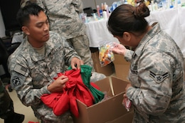 Army Staff Sgt. Reagan Cruz and Air Force Airman 1st Class Tara Lizama stuff holiday stockings for members of Joint Special Operations Task Force-Philippines. Task force members made up nearly 600 stockings from items donated by U.S. citizens, churches, non-profit organizations, and JSOTF-P family members. (U.S. Marine Corps photo by Sgt. Jose Castellon/Released)