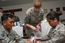 Army Staff Sgt. Reagan Cruz, Air Force Master Sgt. Rose Gould, and Air Force Airman 1st Class Tara Lizama stuff holiday stockings for members of Joint Special::r::::n::Operations Task Force-Philippines. Task force members made up nearly 600 stockings from items donated by U.S. citizens, churches, non-profit organizations, and JSOTF-P family members. (U.S. Marine Corps photo by Sgt.::r::::n::Jose Castellon/Released)