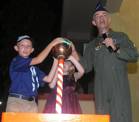 ANDERSEN AIR FORCE BASE, Guam - Col. Tod Fingal, 36th Wing vice commander, receives some assistance from two children during the Holiday Tree Lighting Ceremony here Dec. 3rd. The children wereselected to pull the switch that lit the tree for the first time during the holiday season. (U.S. Air Force photo by Airman 1st Class Julian North)