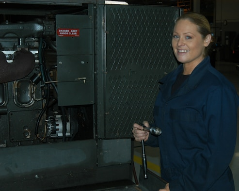 OFFUTT AIR FORCE BASE, Neb. -- Senior Airman Theresa E. Civil, an aerospace ground equipment mechanic with the 55th Maintenance Squadron, poses for a photo in front of a diesel engine driven generator inside the Bennie Davis Maintenance Facility here Dec. 14. The generator is one of many that provide Offutt's aircraft with power while their on the flightline. Airman Civil balances many responsibilities to ensure she is mission ready including taking care of her mother, while being a mom herself. U.S. Air Force Photo by Staff Sgt. James M. Hodgman