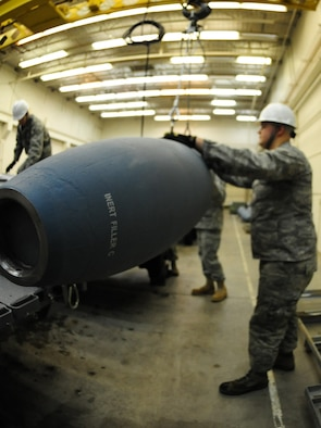 ELLSWORTH AIR FORCE BASE, S.D. -- Airman 1st Class Michael DiRienzo, 28th munitions Squadron conventional maintenance crew member, hold an inert Guided Bomb unit-31 as it is hoisted onto a bomb trailer, Dec. 8.  Airman DiRienzo, along with others, put together several inert GBU-31 bombs for training missions on the B-1B Lancer. (U.S. Air Force photo/Airman 1st Class Anthony Sanchelli)