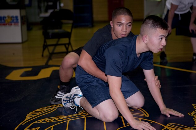 Daniel Weixler (left) prepares to begin a top and bottom drill with Eli Yang during All Marine Wrestling team tryouts at IronWorks Gym here Dec. 14. During the drill, particpants rotated between starting out in the top position and bottom position with the goal being to take control of the match.