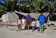 Members of the Hernandez family gather in front of the remains of Carla Hernandez' home in San Agustin, El Salvador, Dec. 14, 2009. November flooding and mudslides claimed more than 100 lives and displaced many more residents. A combined Medical Civil Action Program (MEDCAP) coordinated between U.S. and El Salvadoran officials is providing free medical care to residents of affected areas today and tomorrow. A team of 30 from Joint Task Force-Bravo, based in Honduras, is working with the Salvadoran Ministry of Health and others to provide the care. (U.S. Air Force photo/Tech. Sgt. Mike Hammond)