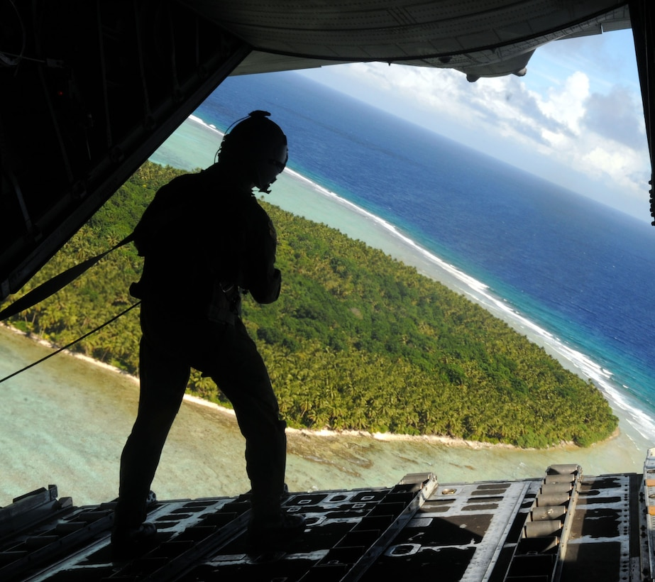 CHUUK ISLANDS - Staff Sgt. Cravenkeo Khamone, 36th Airlift Squadron loadmaster, spots the drop location for a box of donated goods being dropped over the Chuuk Islands Dec. 16 in support of Operation Christmas Drop. The operation, which began in 1952, is the Air Force's longest-running humanitarian mission. Airmen today continue the tradition delivering supplies to remote islands of the Commonwealth of the Northern Marianas Islands, Yap, Palau, Chuuk and Pohnpei.   (U.S. Air Force photo by Airman 1st Class Julian North)