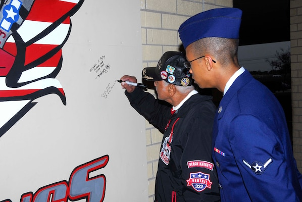 Retired Capt. Claude R. Platte, a former Tuskegee Airman, signs a wall at the 323rd Training Squadron dedicated to the Tuskegee Airmen as his great nephew Airman Christopher Platte, 331st Training Squadron, looks on. Capt. Platte was the first African-American officer to be trained and commissioned in the Air Force pilot training program. (U.S. Air Force photo/Alan Boedeker)
