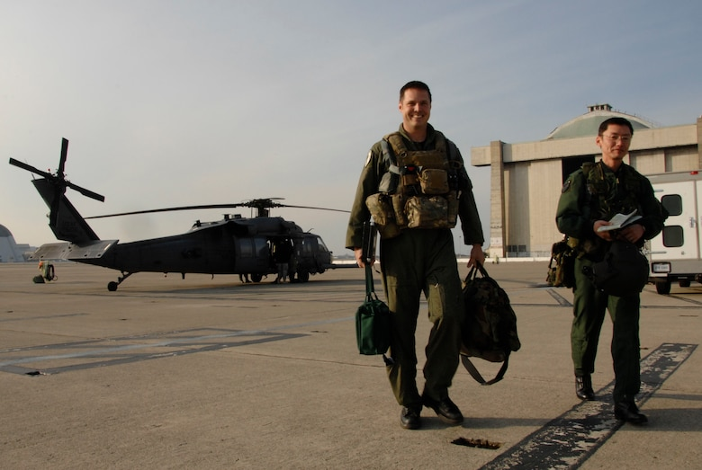 Maj. Mathew Wenthe, a 129th Rescue Squadron tactical officer with the 129th Rescue Wing, Moffett Federal Airfield Calif., and Maj. Eiji Sekine, a Japan Air Self-Defense Force UH-60J pilot with the Air Rescue Wing at Komaki Air Base, Japan, walk away from the HH-60G Pave Hawk after air refueling training Dec. 9, 2009. (Air National Guard photo by Tech. Sgt. Ray Aquino)