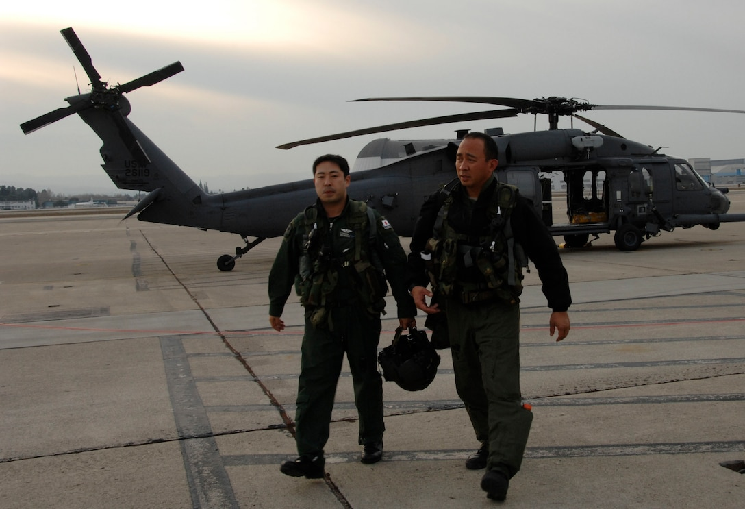 Maj. George Dona (right), an HH-60G Pave Hawk pilot with the 129th Rescue Squadron, Moffett Federal Airfield Calif., and Capt. Takeshi Tokuda (left), a Japan Air Self-Defense Force UH-60J pilot with the Air Rescue Wing at Komaki Air Base, Japan, head back to an operations building after a day of air refueling training Dec. 9, 2009. (Air National Guard photo by Tech. Sgt. Ray Aquino)