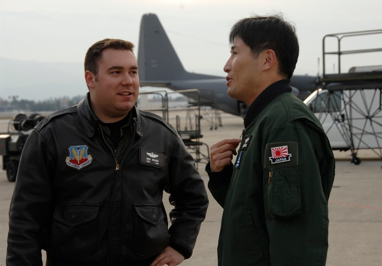 Maj. Masahiko Miyazaki, a Japan Air Self-Defense Force C-130H Hercules pilot with the 1st Tactical Airlift Wing at Komaki Air Base, Japan, speaks with Tech. Sgt. Eric Valdez, an aircraft loadmaster with the 130th Rescue Squadron, Moffett Federal Airfield Calif., about their air refueling training Dec. 9, 2009. (Air National Guard photo by Tech. Sgt. Ray Aquino)