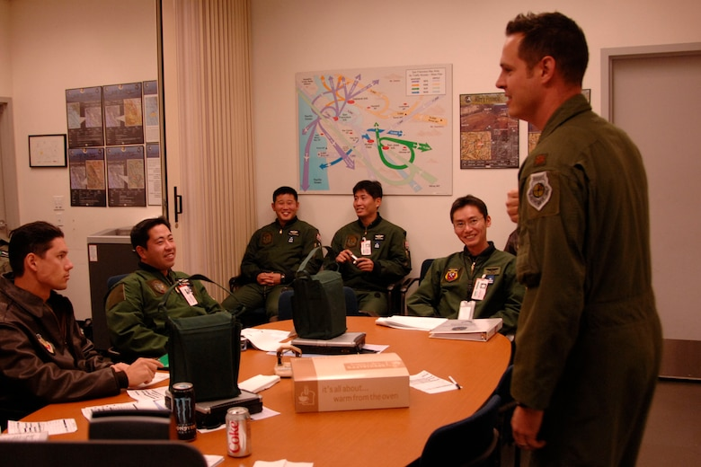 Maj. Mathew Wenthe, a 129th Rescue Squadron tactical officer with the 129th Rescue Wing, Moffett Federal Airfield, Calif,. briefs the Japan Air Self-Defense Force pilots visiting from Komaki Air Base, Japan, about their air refueling training Dec. 10, 2009. (Air National Guard photo by Tech. Sgt. Ray Aquino)