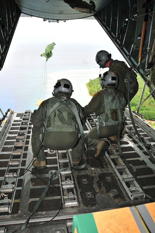 CHUUK, Commonwealth of the Northern Marianas Islands -- Members of the 36th Airlift Squadron watch a bundle of donated goods drop out the back of a C-130 Hercules over a Chuuk island during Operation Christmas Drop Dec. 16. Operation Christmas Drop, the longest running humanitarian airlift mission in the world, delivers supplies to remote islands of the Commonwealth of the Northern Marianas Islands of Yap, Palau, Chuuk and Pohnpei. (U.S. Air Force photo/Tech. Sgt. Kimberly Spinner)