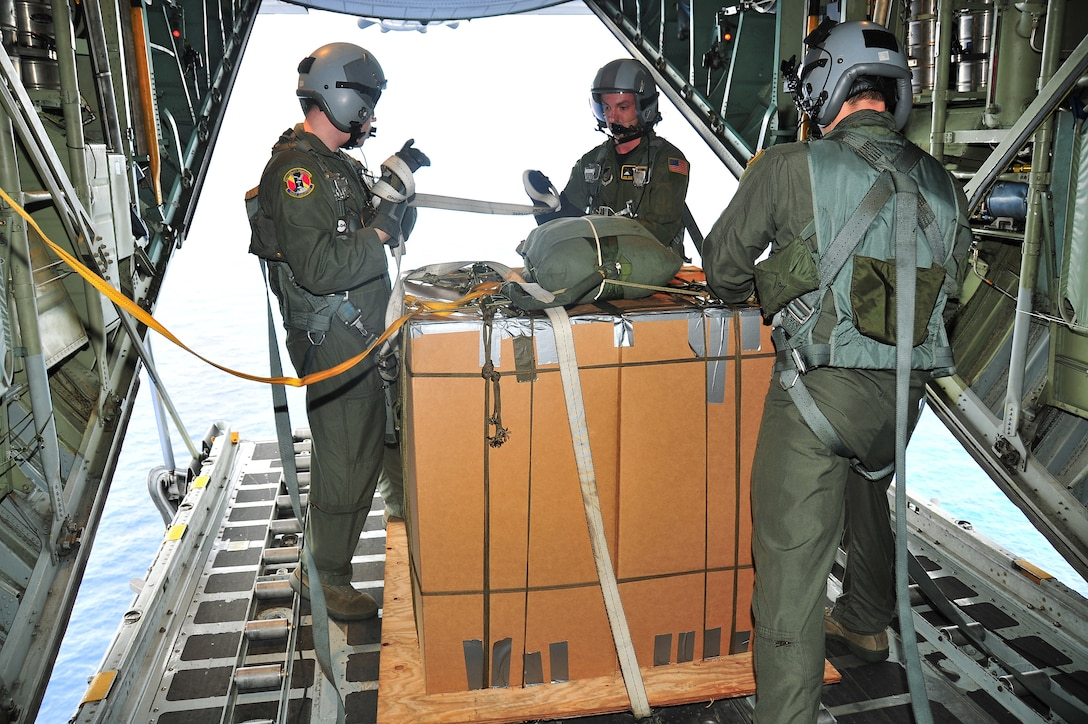 CHUUK, Commonwealth of the Northern Marianas Islands --  (Left to right) Airman 1st Class Jason Barbieri, Senior Airman Dustin DeVeaux, and Lt. Col. David Kincaid, all from the 36th Airlift Squadron, remove cargo straps from the first bundle of donated goods during Operation Christmas Drop Dec. 16. Operation Christmas Drop, the longest running humanitarian airlift mission in the world, delivers supplies to remote islands of the Commonwealth of the Northern Marianas Islands of Yap, Palau, Chuuk and Pohnpei. (U.S. Air Force photo/Tech. Sgt. Kimberly Spinner)