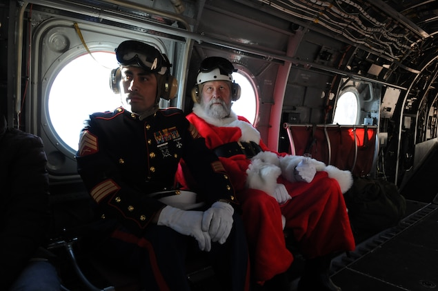 Santa Claus, portrayed by event coordinator Dick McCallum, rides alongside Sgt. Daniel M. Iversen in a CH-46 helicopter en route to the remote village of the Havasupai tribe in order to deliver Christmas gifts to children as part of the Toys for Tots program on Dec. 16, 2009. Iversen, a 31-year-old native of Torrance, Calif., was one of seven Marine reservists from the Phoenix-based Environmental Services Detachment who escorted Santa. Marine Medium Helicopter Squadron 764, a reserve unit based at Edwards Air Force Base north of Los Angeles, has flown toys to the village's children for Christmas as part of the Toys for Tots program for the past 14 years.