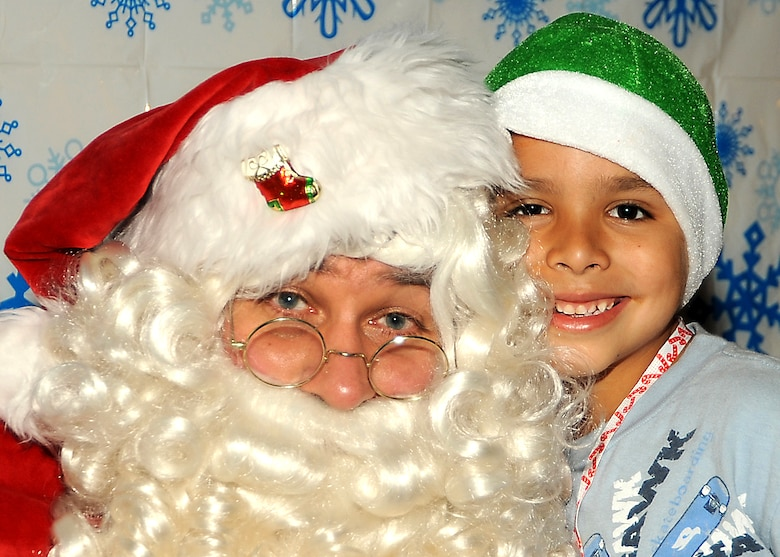 "Mike Ibarra (age 7) poses for a picture with Santa during the ""Candy Land"" children's holiday celebration at Fort MacArthur Hall, San Pedro, Calif., Dec. 12. Los Angeles Air Force Base's Youth Programs provided food, fun and games for children ages 2-11. (Photo by Joe Juarez)"