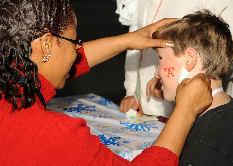 "Patricia Brown (left), Los Angeles Air Force Base Youth Programs director, arranges a holiday ""tattoo"" on a young boy's face during the ""Candy Land"" children's holiday celebration at Fort MacArthur Hall, San Pedro, Calif., Dec. 12. The event provided food, fun and games for children ages 2-11. (Photo by Joe Juarez)"