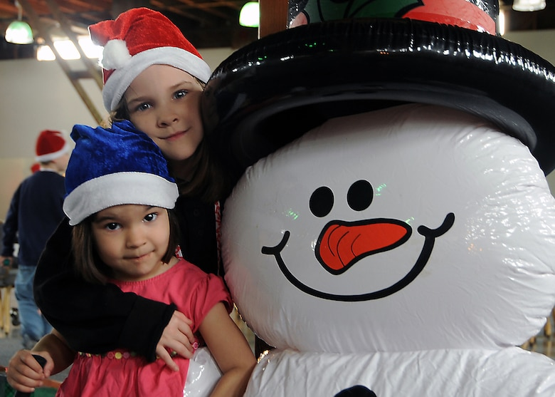 "Athena and Ariel Ruiz pose with Frosty during the ""Candy Land"" children's holiday celebration at Fort MacArthur Hall, San Pedro, Calif., Dec. 12. Los Angeles Air Force Base's Youth Programs provided food, fun and games for children ages 2-11. (Photo by Joe Juarez)"