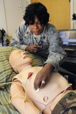 Maj. Phaedra Christenson demonstrates how the Simman can be programmed to simulate realistic symptoms as a training tool. U. S. Air Force photo by Sue Sapp