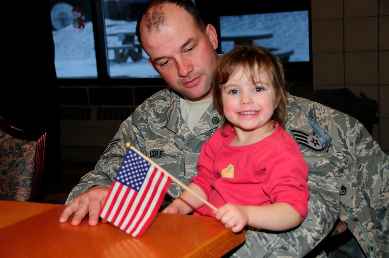 U.S. Air Force Staff Sgt. Mike Cole holds his daughter before saying goodbye as the first wave of Civil Engineers from the 148th Fighter Wing departs Duluth, Minn. Dec. 17th, 2009.  A large number of 148th Civil Engineers will deploy to Bagram Airfield, Afghanistan for approximately six months in late 2009 and early 2010.