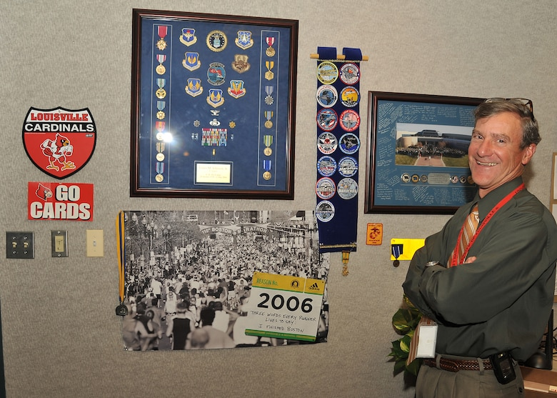 "Mr. Lou Johnson, director of the Space and Missile System Center's Space Logistics Group, ""shows off"" his Boston Marathon photo and medal he received when he completed the Marathon in 2006.  Mr. Johnson was recently recognized for his enduring support and participation in the Air Force Marathons."