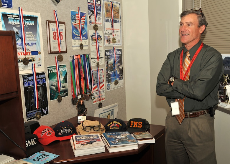 Mr. Lou Johnson, director of the Space and Missile System Center's Space Logistics Group, stands by the posters and medals he's received from past and present Air Force Marathons.  Mr. Johnson has participated in every AF Marathon offered since it's inception in 1997 and was recently recognized for his enduring support and participation in the Air Force Marathons.