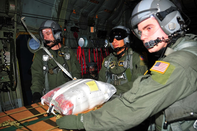CHUUK, Commonwealth of the Northern Marianas Islands -- (left to right) Senior Airman Dustin Deveaux, 1st Lt. Alexander Johns, and Airman 1st Class Jason Barbieri prepare to drop it a bundle of donated goods out the back of a C-130 Hercules aircraft over a Chuuk island during Operation Christmas Drop Dec 16, 2009.  Operation Christmas Drop is the longest running humanitarian mission.  The Air Force delivers supplies to remote islands of the Commonwealth of the Northern Marianas Islands of Yap, Palau, Chuuk and Pohnpei. (U.S. Air Force Photo/Tech. Sgt Kimberly Spinner)