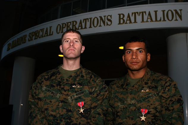 Staff Sgt. Samuel E. Schoenheit and Sgt. Carlos Bolanos stand in front of the 2d Marine Special Operations Headquarters building Jan 17. The Marines each received a Bronze Star Medal with distinguishing device for heroic actions in Afghanistan on June 26, 2008