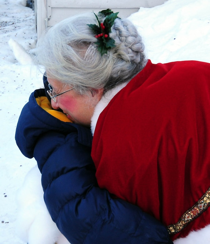 Mrs. Santa gives a goodbye hug to a Gambell child after a Dec. 19, 2009 visit to the Gambell Public School. The Alaska Air and Army National Guard visited the village on remote Bering Sea island of St. Lawrence with Santa and a group of civilian volunteers as part of Operation Santa Claus. Now in its 53rd year, Operation Santa Claus is a program of the Alaska National Guard to bring toys, food, supplies and Christmas cheer to isolated villages around the state. Alaska Air National Guard photo by 1st. Lt. John Callahan.