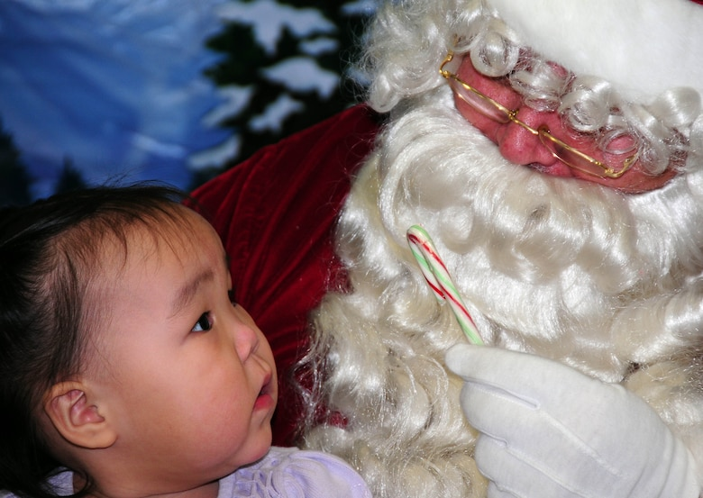 Santa offers a candy cane to Gambell resident Erin Apangalook, age 2. The Alaska Air and Army National Guard were in Gambell, on remote St. Lawrence Island in the Bering Sea, with a group of civilian volunteers on Dec. 16, 2009 as part of Operation Santa Claus. Now in its 53rd year, Operation Santa Claus is a program of the Alaska National Guard to bring toys, food, supplies and Christmas cheer to isolated villages around the state. Alaska Air National Guard photo by 1st. Lt. John Callahan.