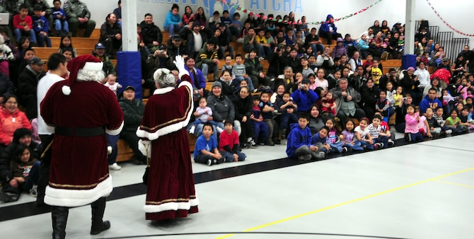 Santa and Mrs. Santa greet excited schoolchildren gathered in the gymnasium at Gambell Public School on Dec. 16, 2009. The Alaska Air and Army National Guard were in Gambell, on remote St. Lawrence Island in the Bering Sea, with a group of civilian volunteers on Dec. 16, 2009 as part of Operation Santa Claus. Now in its 53rd year, Operation Santa Claus is a program of the Alaska National Guard to bring toys, food, supplies and Christmas cheer to isolated villages around the state. Alaska Air National Guard photo by 1st. Lt. John Callahan.