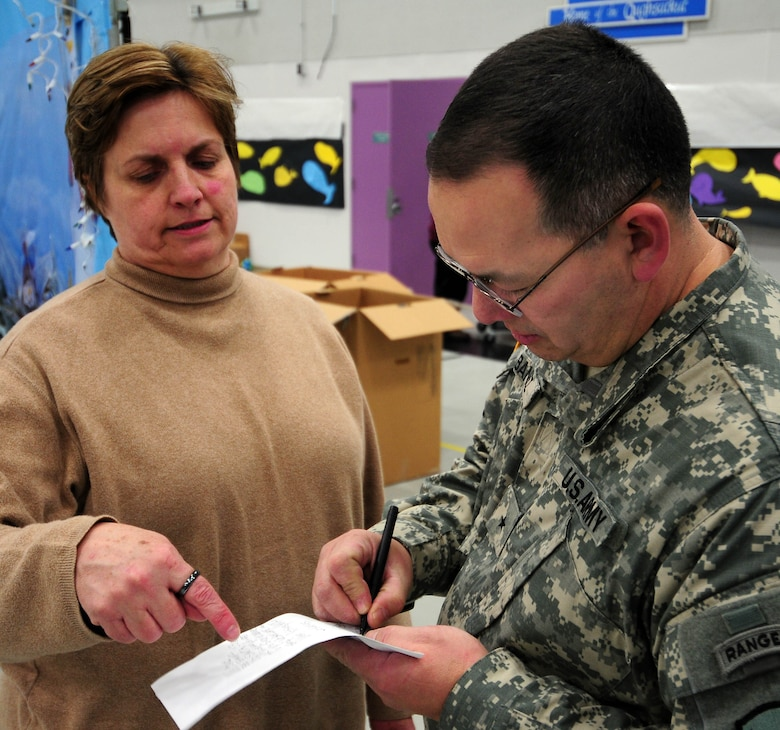 Brig. Gen. Randy Banez (right), assistant adjutant general for the Alaska Army National Guard, prepares short remarks for schoolchildren at Gambell Public School with help from Jan Meyers, the Alaska National Guard's state family programs director. The Alaska Air and Army National Guard were in Gambell, on remote St. Lawrence Island in the Bering Sea, with a group of civilian volunteers on Dec. 16, 2009 as part of Operation Santa Claus. Now in its 53rd year, Operation Santa Claus is a program of the Alaska National Guard to bring toys, food, supplies and Christmas cheer to isolated villages around the state. Alaska Air National Guard photo by 1st. Lt. John Callahan.