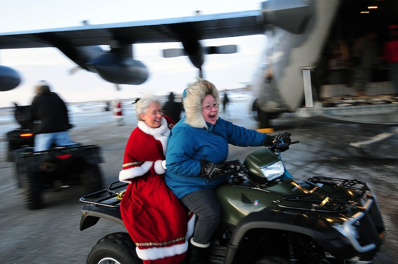 Gambell resident Betsy Katongan whisks Mrs. Santa by an Alaska Air National Guard HC-130 transport aircraft on their way to the Gambell Public School. The Alaska Air and Army National Guard were in Gambell, on remote St. Lawrence Island in the Bering Sea, with a group of civilian volunteers as part of Operation Santa Claus 2009. Now in its 53rd year, Operation Santa Claus is a program of the Alaska National Guard to bring toys, food, supplies and Christmas cheer to isolated villages around the state. Alaska Air National Guard photo by 1st. Lt. John Callahan.