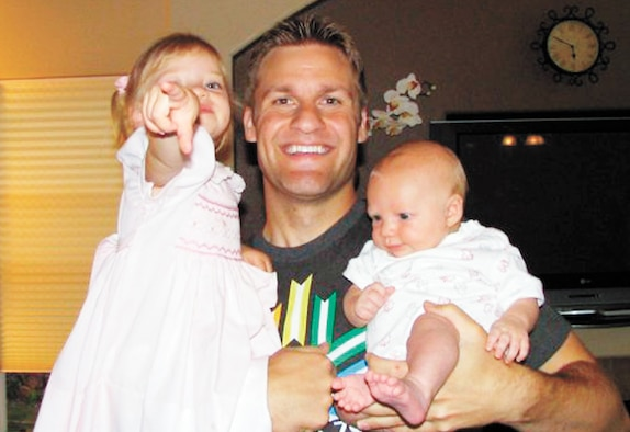 """Capt. Jesse Goolsby poses for a photo with his two daughters in this photo taken in the Goolsbys' home. The captain's most recent work, a short story called """"Thirteen Steps,"""" is scheduled to be published in Storyglossia magazine in February. (U.S. Air Force photo)"""