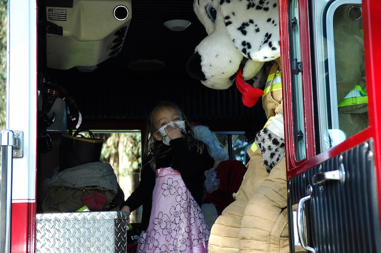 "VANDENBERG AIR FORCE BASE, Calif. -- Getting ready to make her grand entrance at the assembly, Makaila Lubas, daughter of Senior Master Sgt. Frank Lubas, boards a Vandenberg fire truck here Friday, Dec. 18, 2009, with Spot the Fire Dog and Santa. After learning of Makaila's diagnosis of leukemia, the students at Crestview Elementary School raised more than $1,600 during the fundraiser deemed ""Pennies for Makaila"" and presented her a check during the assembly. (U.S. Air Force photo/Airman 1st Class Heather R. Shaw)"