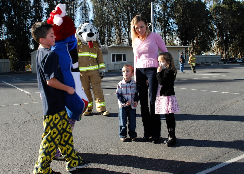 VANDENBERG AIR FORCE BASE, Calif. -- In an effort to ensure Makaila Lubas, daughter of Senior Master Sgt. Frank Lubas of the 14th Air Force, has a good Christmas, Trevor Middleton, son of Tech. Sgt. Michael Middleton of the 14th Air Force, helps present her with a stocking filled with gifts here Friday, Dec. 18, 2009. Makaila was diagnosed with leukemia in October and, after hearing about her diagnosis, the students at Crestview Elementary School worked together to raise money and provide her with gifts. (U.S. Air Force photo/Airman 1st Class Heather R. Shaw)