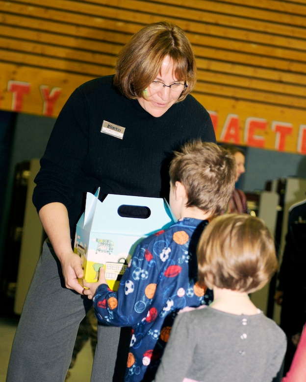 Dorothy Choate hands out Cuzzie Cares Deployment Kits at Ramstein Elementary School Dec. 17, 2009, at Ramstein Air Base, Germany. Cuzzie, designed by Trevor Romain, is an inventive bear that creates flying machines with the help of his ground crew and is the centerpiece of a new kit designed to comfort school-age children during deployments. Ms. Choate is the 86th Services Squadron family member program flight chief. (U.S. Air Force photo/Airman 1st Class Brea Miller)