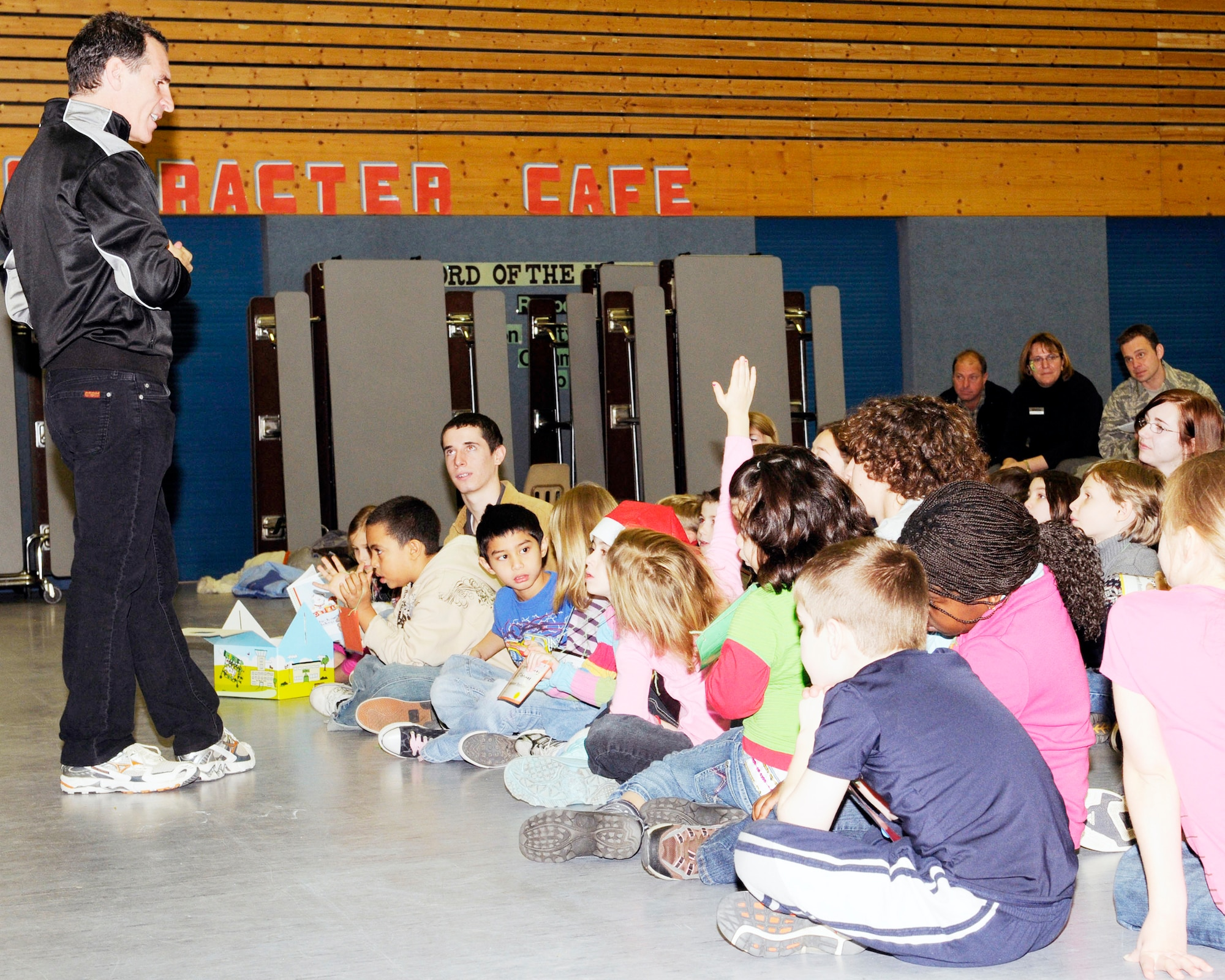 """Trevor Romain answers questions from youth at Ramstein Elementary School Dec. 17, 2009, at Ramstein Air Base, Germany. Mr. Romain, a children's author, is the creator of the Air Force Family focused campaign, """"Cuzzie the Bear"""" designed to comfort school-age children while their parents are deployed. (U.S. Air Force photo/Airman 1st Class Brea Miller)"""