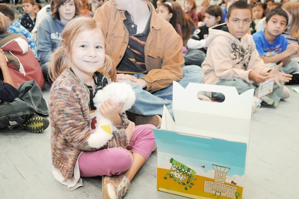 Natalie Zenk, 6, smiles after receiving one of the first Cuzzie Cares Deployment Kits Dec. 17, 2009, at Ramstein Air Base, Germany. These kits, designed to comfort school-age children during their parent's deployment, contain journals, stationary, photo albums, countdown calendars, post cards, playing cards, dog tags and a special friend, Cuzzie the Bear. Natalie is the daughter of Capt. Micheal Zenk from the 86th Aeromedical Evacuation Squadron. (U.S. Air Force photo/Airman 1st Class Brittany Perry)