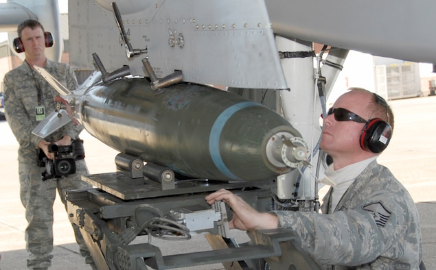 """Tech Sgt. Josh Jones, left, a member of the 188th Fighter Wing, records video footage of the 188th's Master Sgt. Albert Wright as he loads an MK-82, 500-pound bomb during initial certification training on an A-10C Thunderbolt II """"Warthog"""" Nov. 7, 2009. Jones, who is the head football coach at Magazine High, was named Class 2A Coach of the Year by Hooten's Arkansas Football, the state's largest sports publication that focuses on football. Jones' Magazine Rattlers set multiple school records, including wins, playoff victories, total offense and points scored. Jones has been a member of the 188th for 14 years. (U.S. Air Force photo by Tech Sgt. Stephen Hornsey/188th Fighter Wing Public Affairs)"""