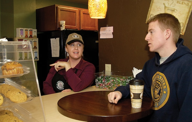 """On a cold Friday night, Navy Fleet Reconnaissance THREE Airman Michael Wilson gets a free coffee and a warm, friendly greeting by volunteer Staff Sgt. Lisa Vincelette at the chapel-sponsored Latté Lounge. Located in Loop Hall, Bldg. 5913, the lounge offers Airmen a positive, upscale place to play billiards or electronic games, meet friends and get free café-type refreshments. Sergeant Vincelette is an IMA and chaplain assistant who also donates many hours at the Lounge. She says being a part of such an outreach is exciting. """"It charges me,"""" she says. """"You know, they say it's more blessed to give than receive."""" (Air Force photo by Margo Wright)"""