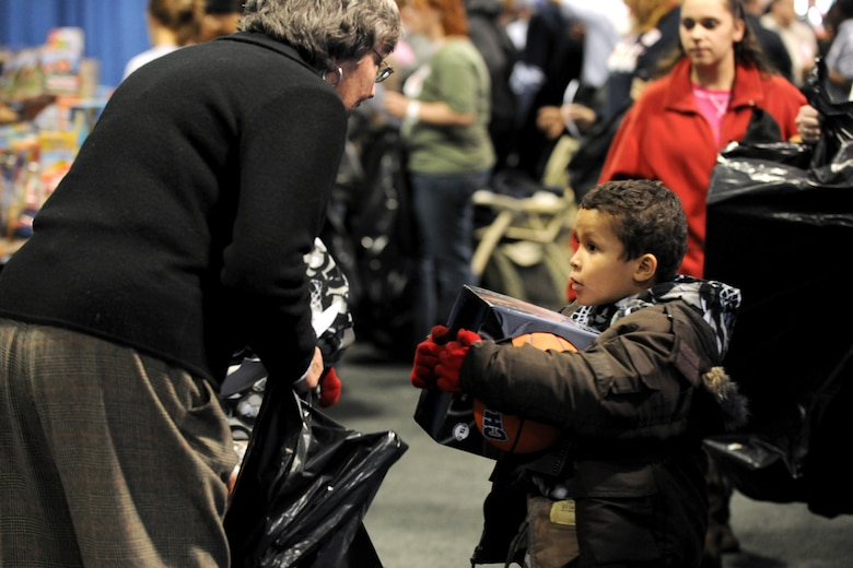 A young boy picks out a basketball as his gift for Christmas this year with the help a Salvation Army volunteer at the Oncenter Complex in Syracuse, NY on 22 Dec. 2009. The boy and his family were participating in the Annual Christmas Bureau Salvation Army Food and Gift drive supplying needy families with gifts for their children and food for their Holiday meal. (US Air Force photo by Tech. Sgt. Jeremy M. Call/Released)