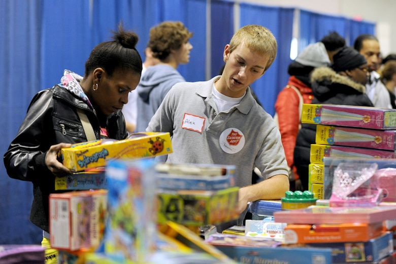 Syracuse area resident volunteer Alex assists a local mother in finding gifts for her children at the Oncenter Complex in Syracuse, NY on 22 Dec. 2009. Alex was a volunteer personal shopper at the Annual Christmas Bureau Salvation Army Food and Gift drive supplying needy families with gifts for their children and food for their Holiday meal. (US Air Force photo by Tech. Sgt. Jeremy M. Call/Released)