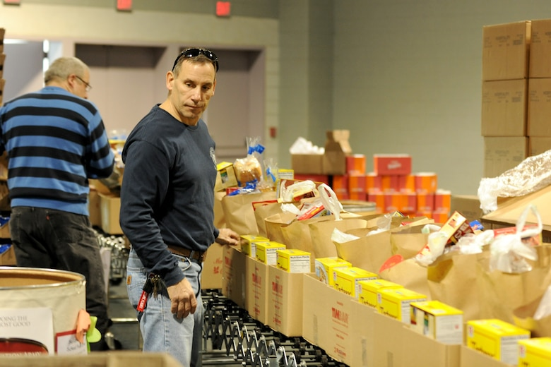 New York State Fire Fighter Mr. Timothy Bak fills boxes at the Oncenter Complex in Syracuse, NY on 22 Dec. 2009. Bak was volunteering at the Annual Christmas Bureau Salvation ArmyFood and Gift drive supplying needy families with gifts for their children and food for their Holiday meal. (US Air Force photo by Tech. Sgt. Jeremy M. Call/Released)