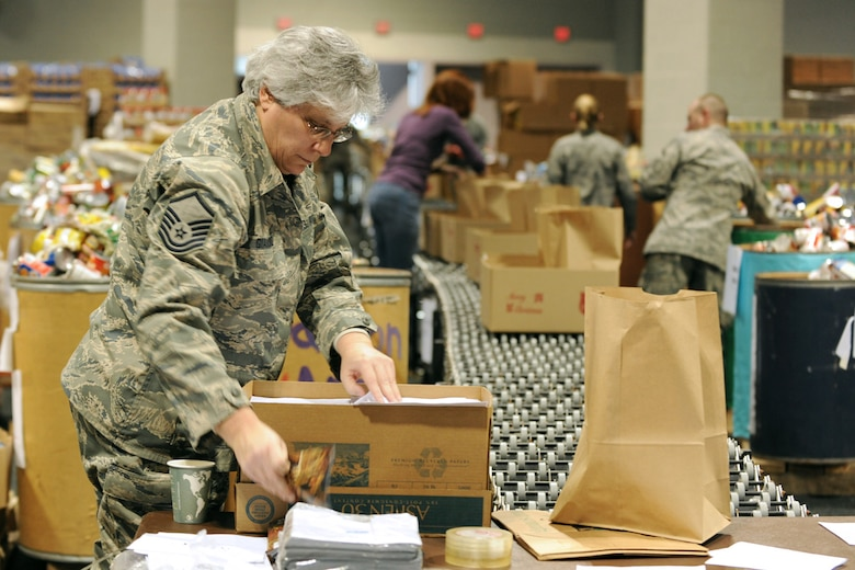 US Air Force Master Sgt. Donna M. Giambalvo packs a box at the Oncenter Complex in Syracuse, NY on 22 Dec. 2009. Giambalvo was volunteering at the Annual Christmas Bureau Salvation Army Food and Gift drive supplying needy families with gifts for their children and food for their Holiday meal. (US Air Force photo by Tech. Sgt. Jeremy M. Call/Released)