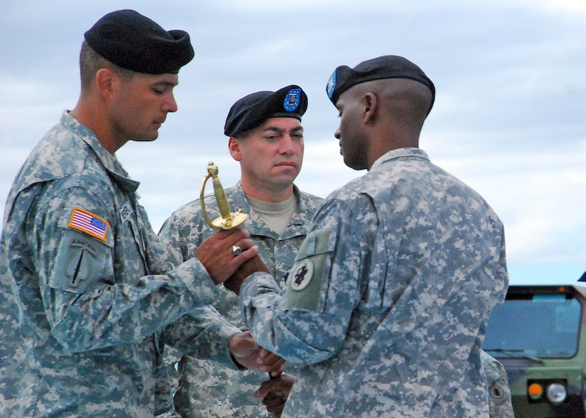 Outgoing 1st Battalion, 228th Aviation Regiment Command Sgt. Maj. Carlos Escalera passes the Non-commissioned Officer Sword to Lt. Col. Salome Herrera, 1/228th commander during a change of responsibility ceremony Dec. 29 here. The NCO Sword was then passed to Command Sgt. Maj. Lucio DeAnda as he assumes responsibilities as the 1/228th command sergeant major. (Photo by U.S. Air Force Staff Sgt. Bryan Franks)
