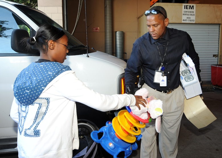 Maria Simmons hands a toy to a staff member at the Union Rescue Mission, Los Angeles, Dec. 18.  Maria and other members from the Los Angeles Air Force Base Youth Programs delivered a van full of toys, clothing and other items collected through donations from the base's Airman & Family Readiness Center, the Airmen's Attic and several families on base. The event was part of YP's Community Out Reach Program, which teaches youths the importance of humanity and caring for others. (Photo by Joe Juarez)