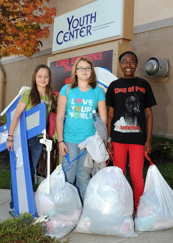 (left to right) Kattie Wesseling, Ashlee Reed and Maria Simmons are ready with bags of toys, clothing and other items to be delivered to the Union Rescue Mission, Los Angeles, to help those in need during this holiday season, Dec. 18.  The girls from the Los Angeles Air Force Base Youth Programs, along with YP leaders, delivered a van full of items collected through donations from the base's Airman & Family Readiness Center, the Airmen's Attic and several families on base. The event was part of YP's Community Out Reach Program, which teaches youths the importance of humanity and caring for others. (Photo by Joe Juarez)